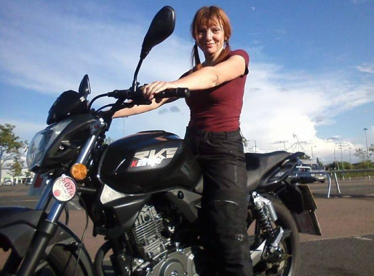 Sharon is sat on her 125 smiling in the sunshine