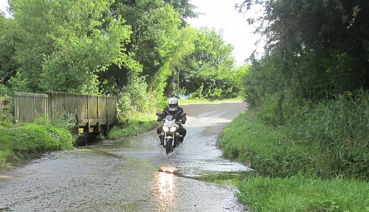 A motorcycle and rider splash through a small ford on a leafy lane