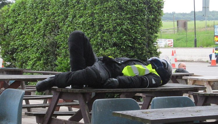 a motorcyclist lies on an outside table in all his motorcycle gear and helmet