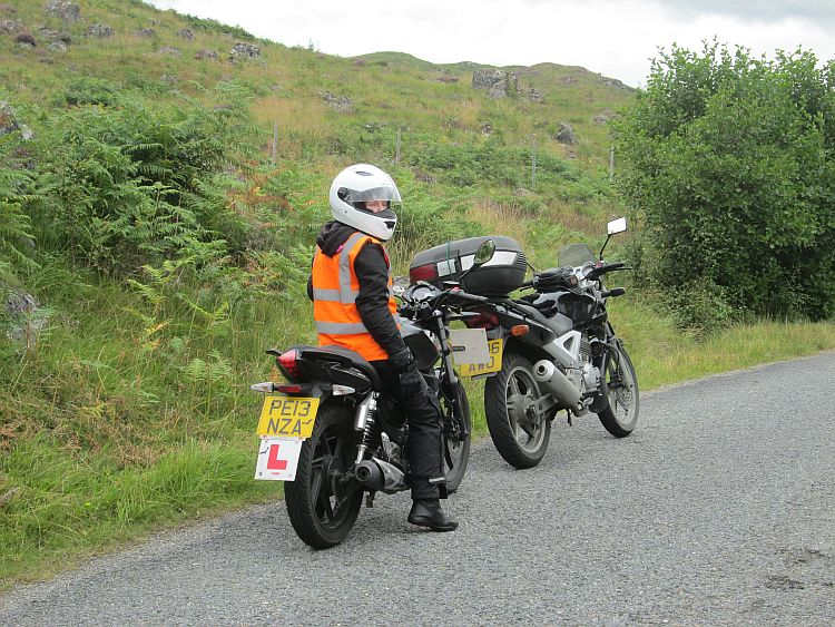 the gf on her bike, Ren's 250 in front, luch green hillside at rannoch