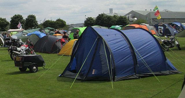 a large blue tent and a small trailer at a motorycle rally