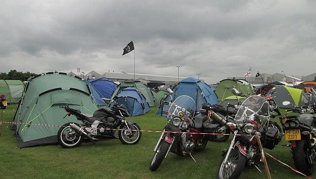 a collection of modern tents among the motorcycles at a rally