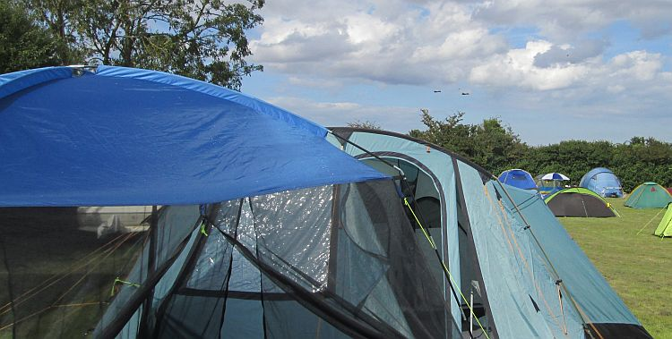 tents in a field, you can just make out the outline of 2 lancaster bombers in the blue sky
