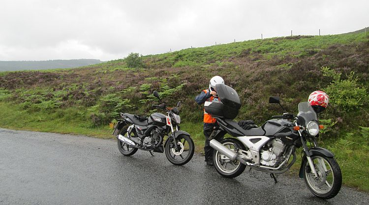 the gf rummages in my top box on a wet, misty highland road