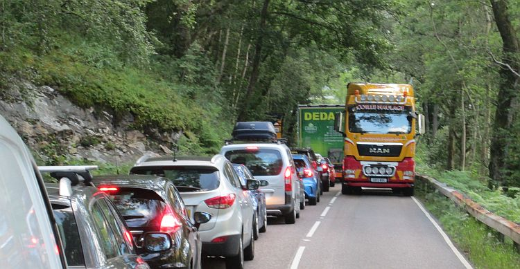 A line of cars with trucks approaching on a busy day near Loch Lomond