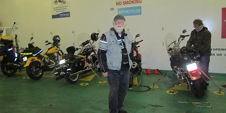 A CMA member stands in the bowels of the ship next to the motorcycles strapped down