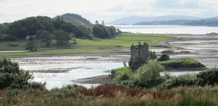 Castle Stalker, a ruin set against a beautiful loch and hills