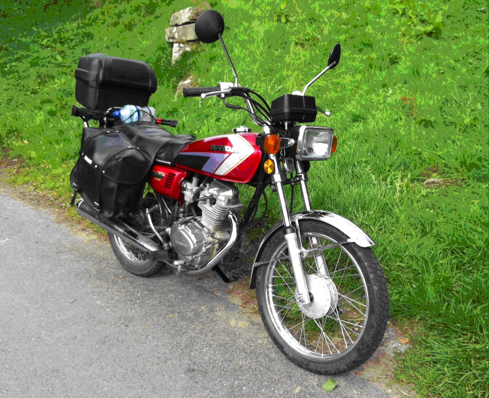 A classic Honda CG 125 in red complete with top box and saddle bags for touring