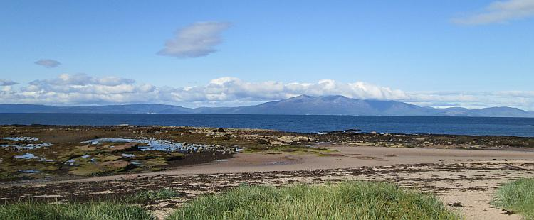Looking across the waters to the Isle of Arron. Mountains in the distance.