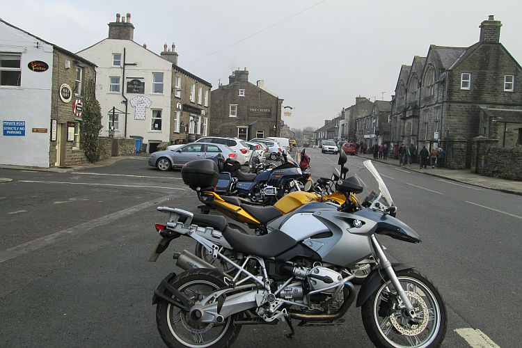 A line of motorcycles parked along the road at Hawes