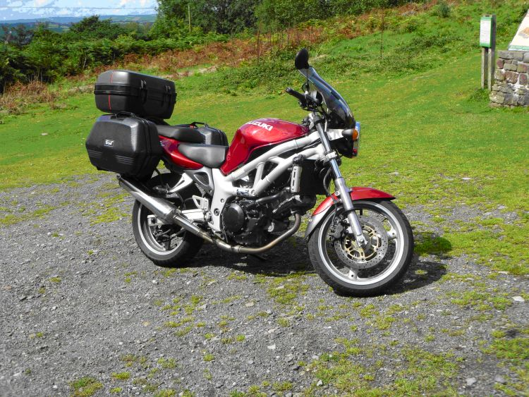 Suzuki's SV 650 in a deep red. Complete with hard luggage and screen