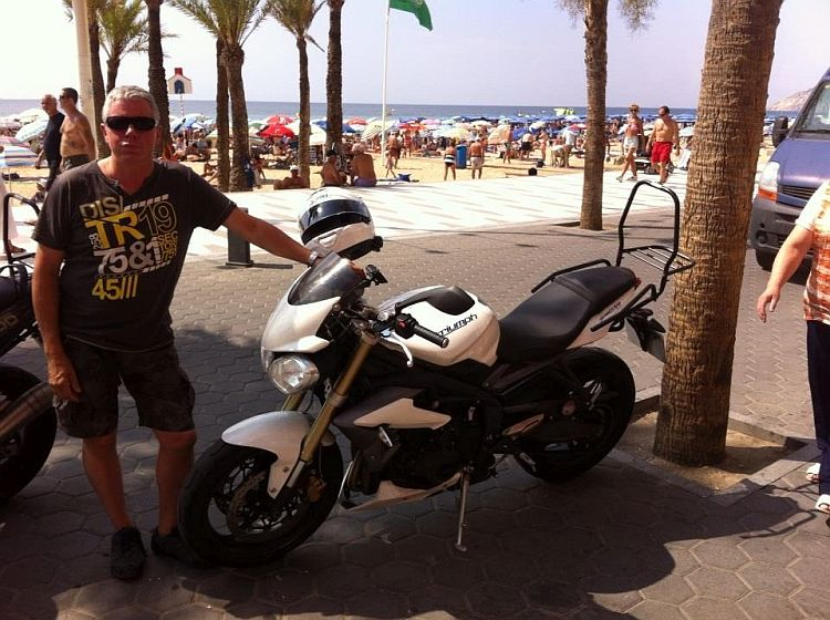 Latchy poses next to his Triumph Street Triple on a benidorm beach
