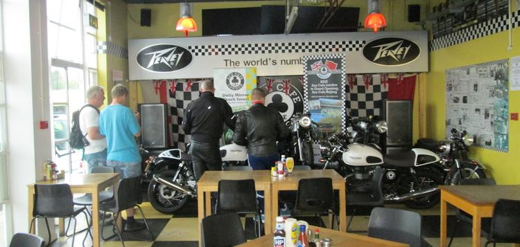 a few vintage motorcycles in a corner of the ace cafe with people looking at them