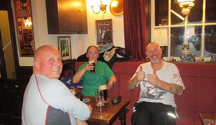 3 riders drinking, smiling and giving the thumbs up at the pub in Kirky stephen