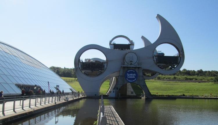 the large falkirk wheel in mid turn. nest to is is a large shing glass building,