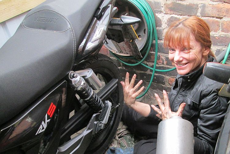 Sharon holds up her dirty hands while working on the bike