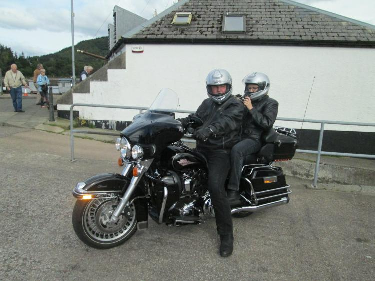 a couple on board a large big black harley davidson motorcycle at inverary