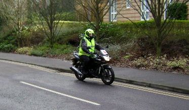 hugo riding along the road on his bike, all kitted up and with bright jacket