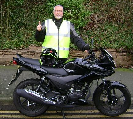 hugo stands next to his shiny black cbf 125 with a smile and thumbs up