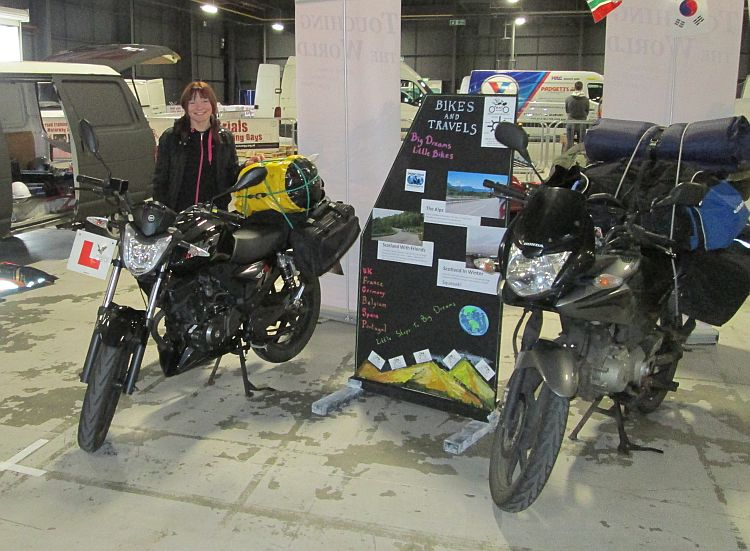 Sharon stands next to our bikes and our board at the manchester bike show