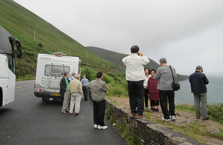 Oriental tourists, the campervan and coach overlooking a bay in Ireland