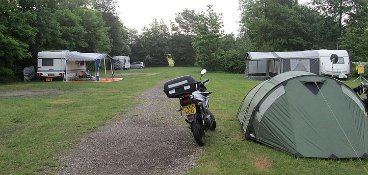 The tent and the 125cc motorcycles at the campsite, with caravans near by