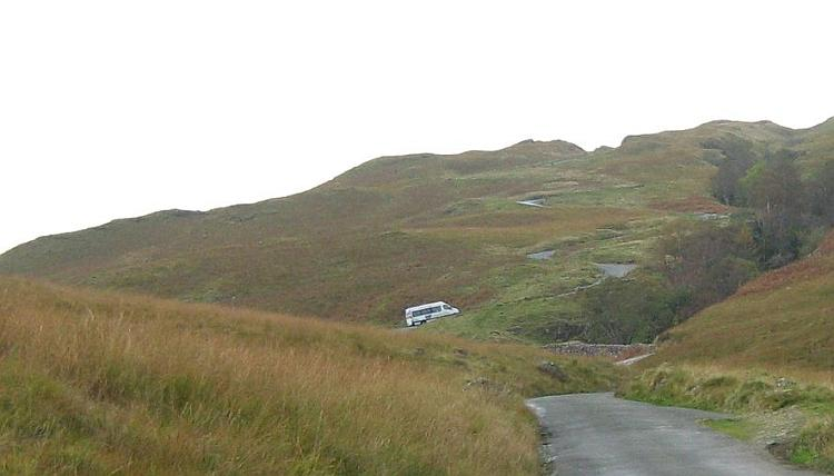 A van crawls up a steep twisty road on The Hardknott Pass