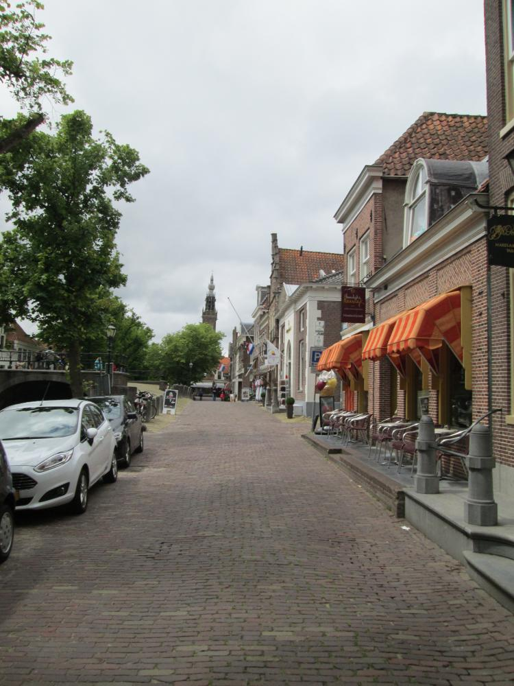 A typical Dutch street, canal, block paved roads, shops, cafes and trees