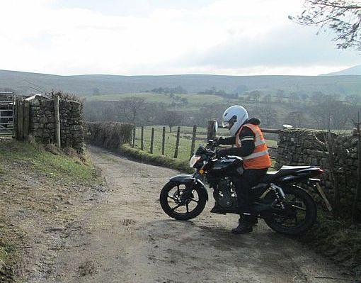 Sharon battles with her 125 on a narrow farm track in the lake district