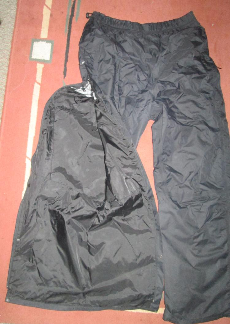 A pair of berghaus deluge waterproof pants with the full leg zip shown open