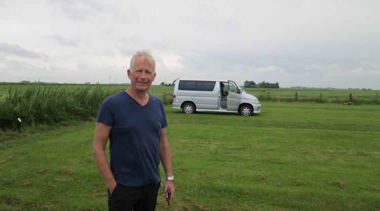 David stands in a camping field in front of his small campervan