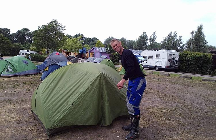 David finishes putting up his tent with a smile
