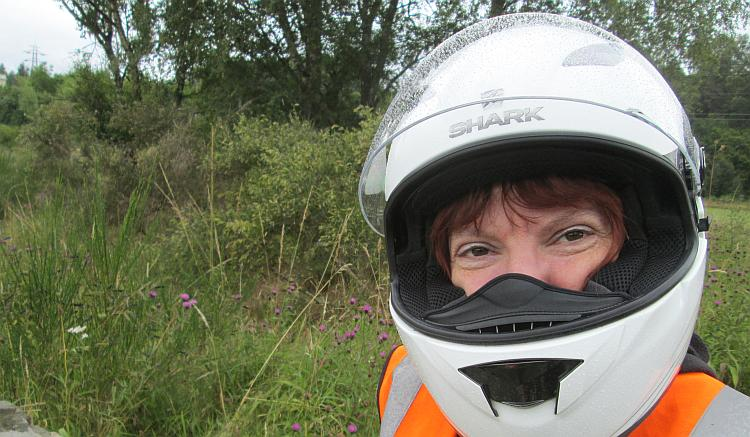 Sharon looks wryly at the camera with her helmet still on