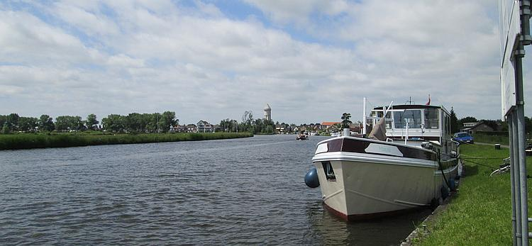 A broad river or canal, a boat and open countryside and trees in The Netherlands