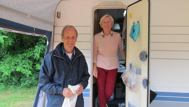 2 very friendly and helpful Dutch caravanners smile to the camera from their caravan