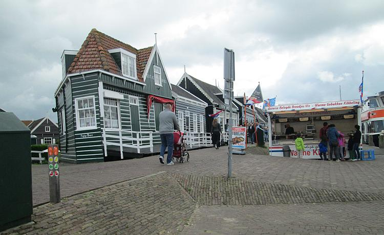 An old wooden dutch house next to a hot dog van in marken
