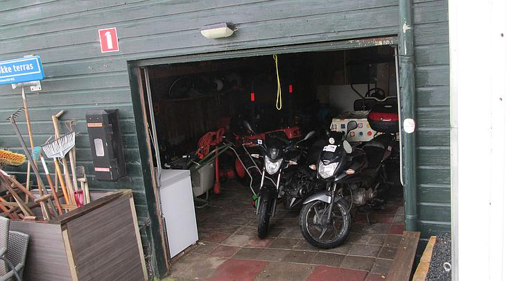 The 2 bikes parked in the garage next to the small tractors