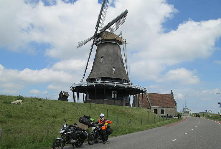 An old Dutch windmill with 2 motorcycles parked in front