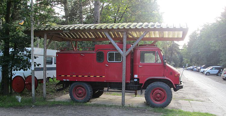 An old Unimog fire truck under a wooden canpoy
