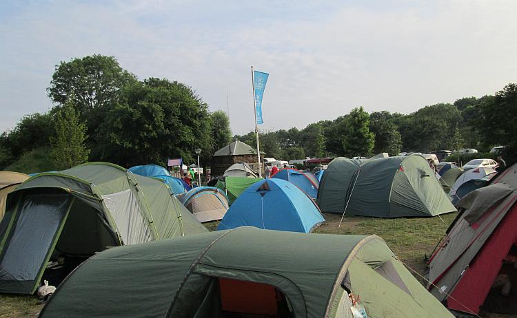 Lots of tents squashed into a small dusty patch of land at caming zeeburg in amsterdam