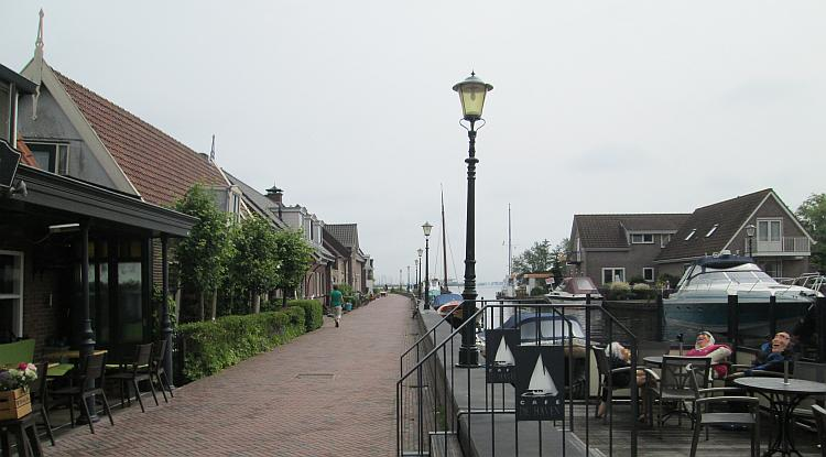 A narrow lane with block paving and houses runs next to a canal in Holland