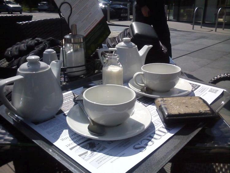 Modern white posh tea pots and cups in the sunshine at a cafe in the Lakes