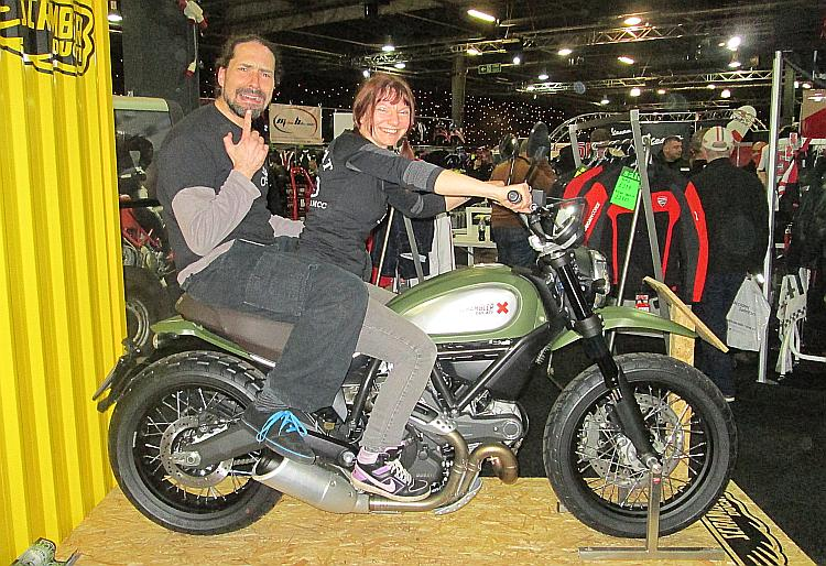 Sharon and Ren sat on a Ducati at a bike Show. Ren is on the back and looks scared