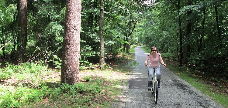 Sharon rides the white cycle through the trees - wearing her motorcycle boots!
