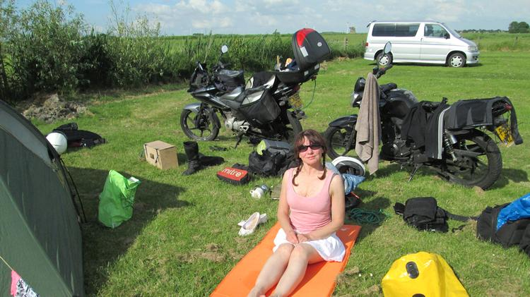 Sharon sits on the grass surrounded by the camping gear, smiling in the sun