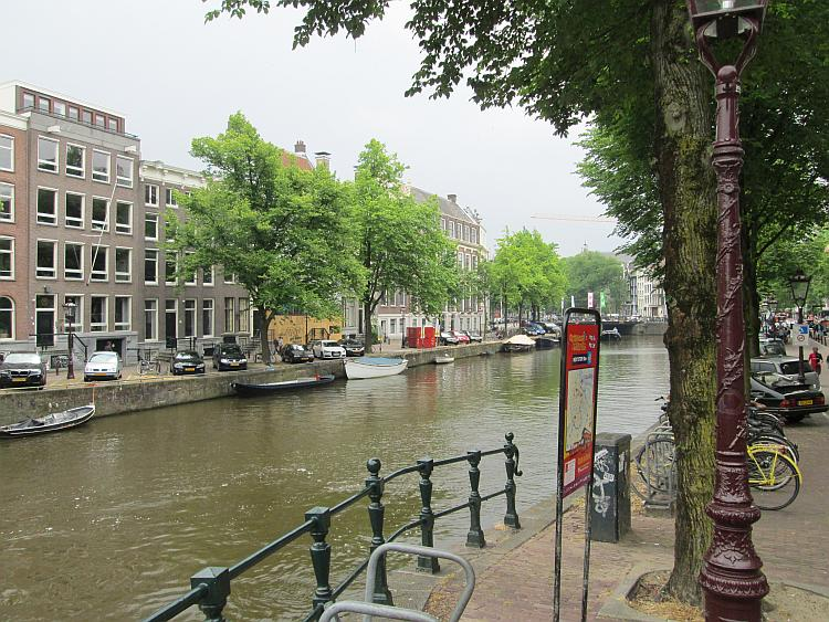 tall houses, canals, bicycles and boats, the scene of a street in Amsterdam