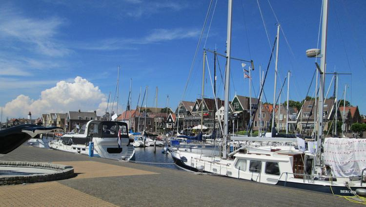 Blue skies, yachts and sailing boats, dutch houses and a smart clean harbour in Urk