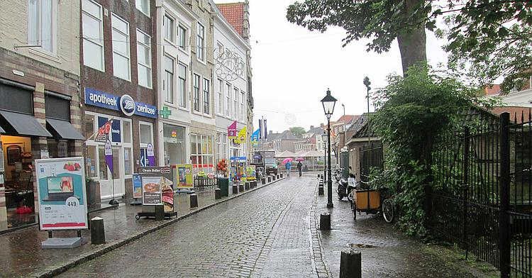 A boots chemist and various other shops along a very wet street in Zierikzee