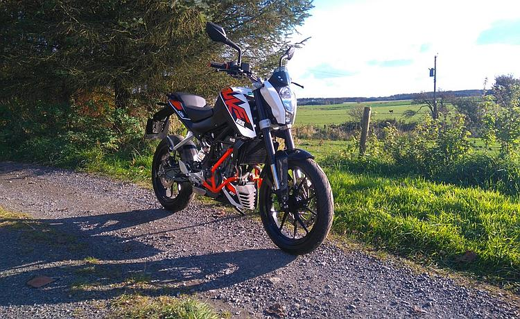Tony's KTM 125 Duke resplendent in the sunshine and countryside