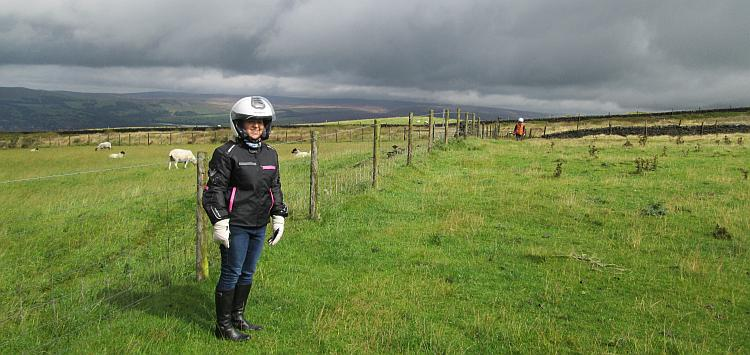 Paula stand on a windswept hill as grey clouds form above.